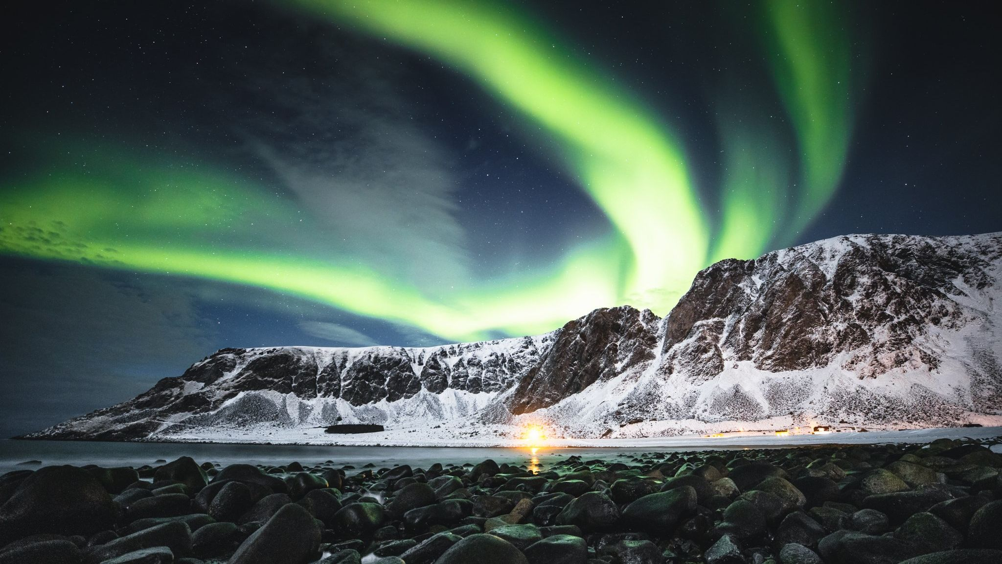 The Northern lights shine brightly across the mountains and the beach below.